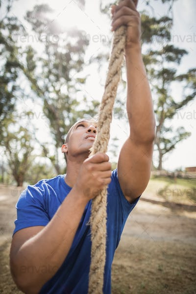 Fit man climbing rope during obstacle course