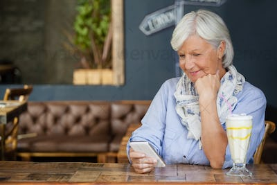 Senior woman using mobiole phone while sitting at table