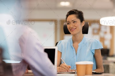 Smiling businesswoman discussing with male colleague in office