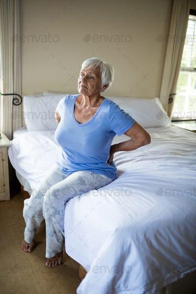 Senior woman suffering from backache in the bedroom
