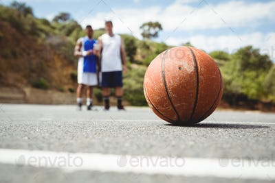 Orange basketball on ground with player standing in background