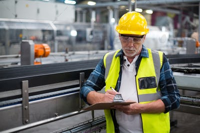 Male factory worker maintaining record on clipboard