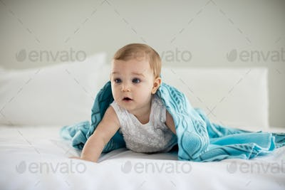 Cute baby girl under the blanket on bed
