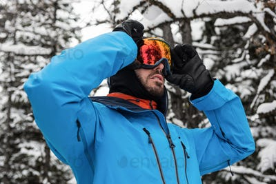 Skier adjusting his sunglasses