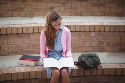 Attentive schoolgirl reading book in campus