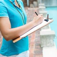 Female coach writing on clipboard near poolside