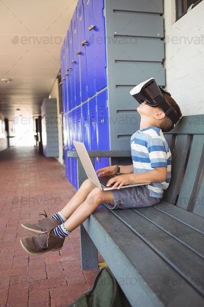 Side view of boy using laptop and virtual reality glasses while sitting on bench