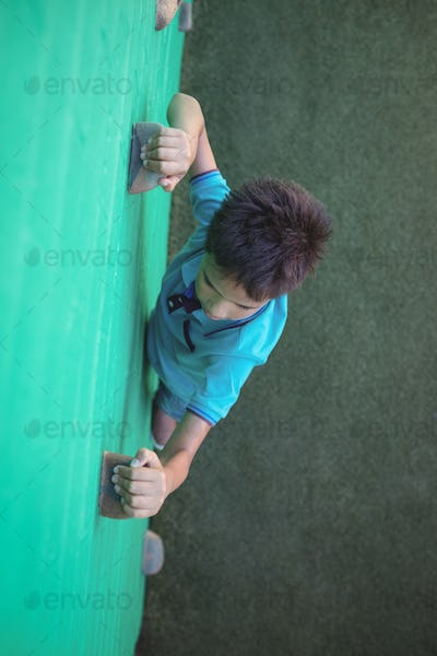 Boy gripping climbing holds on wall