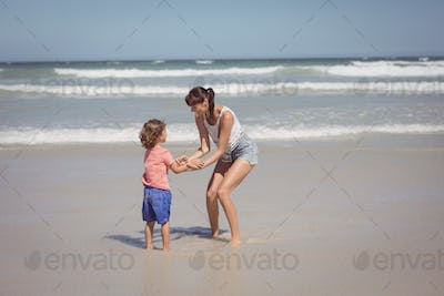 Happy son enjoying with mother on shore at beach