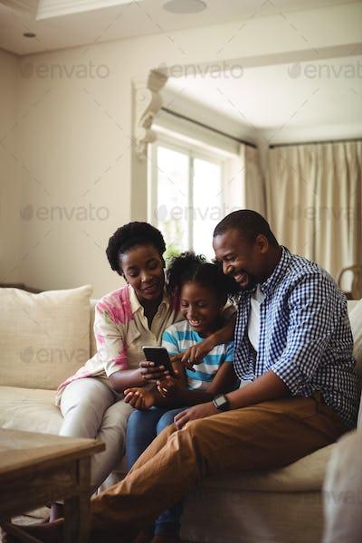 Family using mobile phone in living room