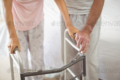 Mid section of senior man helping woman to walk with walker