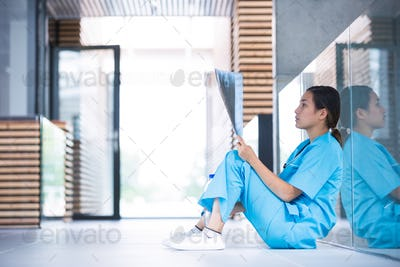 Stressed nurse examining X-ray report