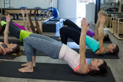Women performing stretching exercise on exercise mat