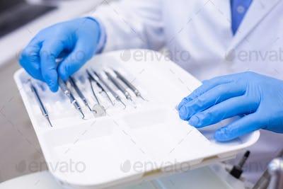 Dentist picking up dental tool