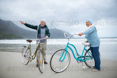Senior couple standing with bicycles on the beach