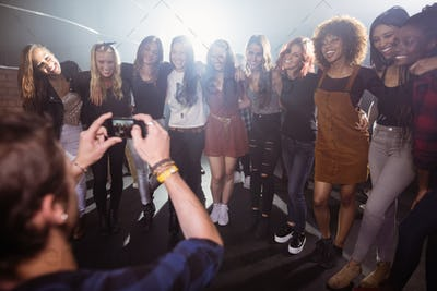 Man photographing happy female friends at nightclub