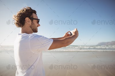 Happy man taking selfie against blue sky at beach