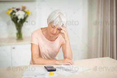 Tensed senior woman sitting in kitchen