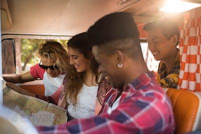 Smiling friends reading map in camper van