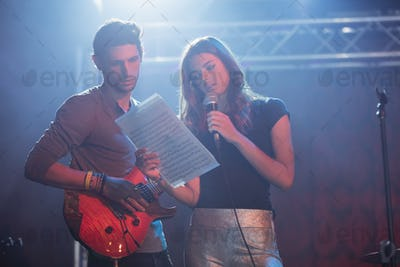 Female singer with male guitarist practicing at nightblub