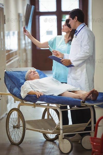 Doctor and nurse examining report in corridor
