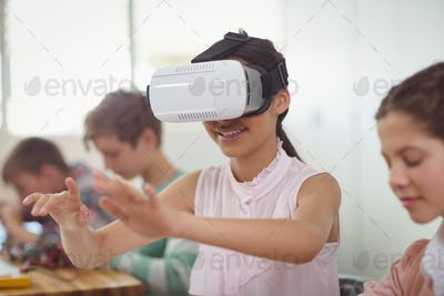 School girl sitting in classroom using virtual reality headset