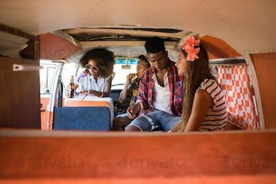 Young friends sitting in camper van