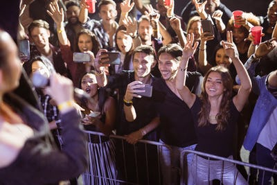 Cheerful young fans photographing performer at nightclub