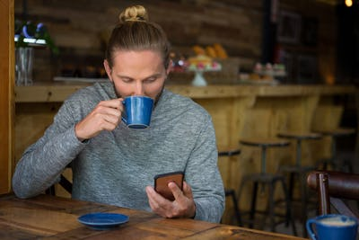Man drinking coffee while using smart phone in cafe