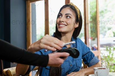 Smiling woman making payment on credit card reader