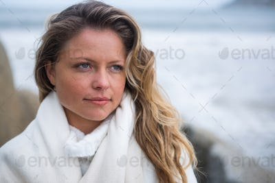 Thoughtful woman wrapped in shawl