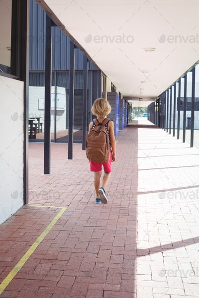 Rear view of schoolboy with backpack walking in corridor