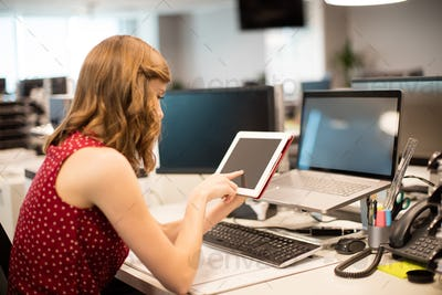 Side view of businesswoman using digital tablet in office