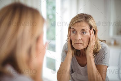 Frustrated senior woman looking at mirror