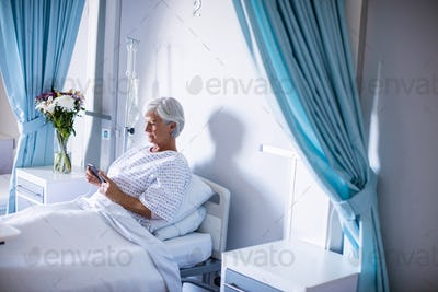 Female senior patient using mobile phone on bed