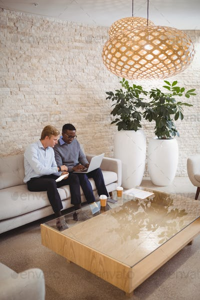 Attentive executives using digital tablet and laptop
