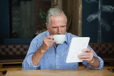 Senior man using digital tablet while drinking coffee