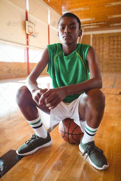 Portrait of teenage boy sitting on basketball