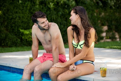 Young couple interacting with each other at poolside