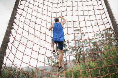 Man climbing a net during obstacle course