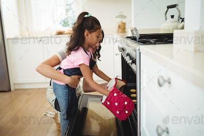 Mother and daughter placing tray of cookies in oven