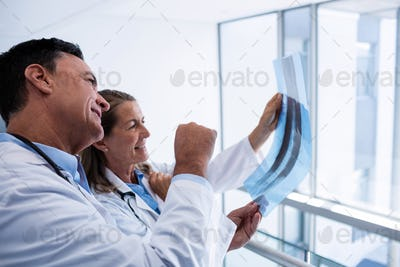 Male and female doctor discussing over x-ray report