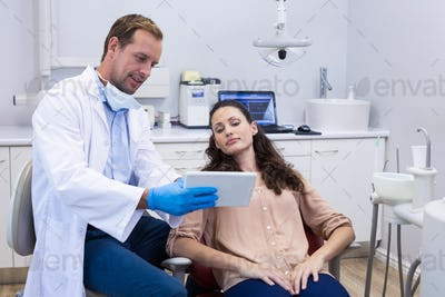 Dentist discussing over digital tablet with female patient