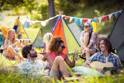 Group of friends having fun together at campsite