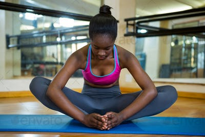 Fit woman doing stretching exercise on mat