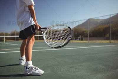Girl holding tennis racket while standing on court
