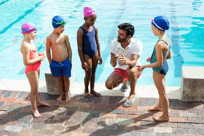 Instructor training children at poolside