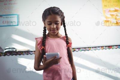 Girl using mobile phone against wall in school