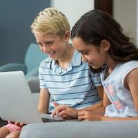 Smiling siblings using laptop in living room