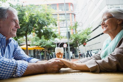 Senior couple holding hands in outdoor café